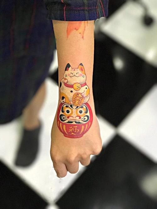 Mẫu tattoo mèo thần tài và daruma ở tay điệu đà