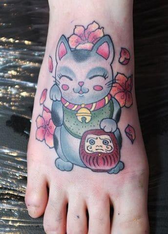 Nhẹ nhàng và nữ tính với kiểu tattoo mèo thần tài và daruma ở chân